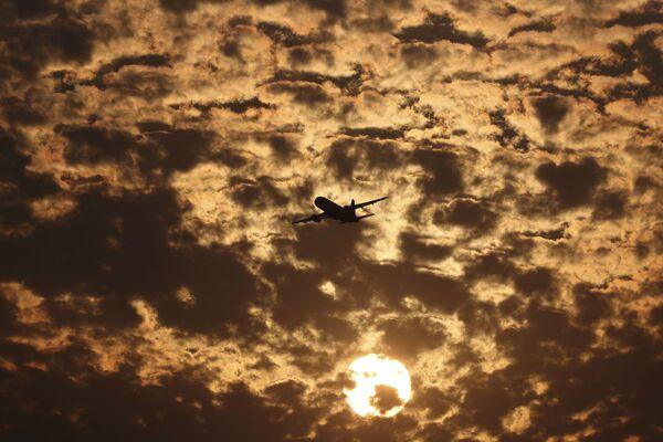 Silueta letadla na pozadí plápolajících mraků během západu slunce v Ahmadábádu, Indie - Sputnik Česká republika