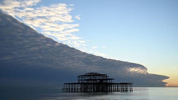 Mraky připomínající obrovskou vlnu nad pláží v Brightonu na jihu Anglie - Sputnik Česká republika