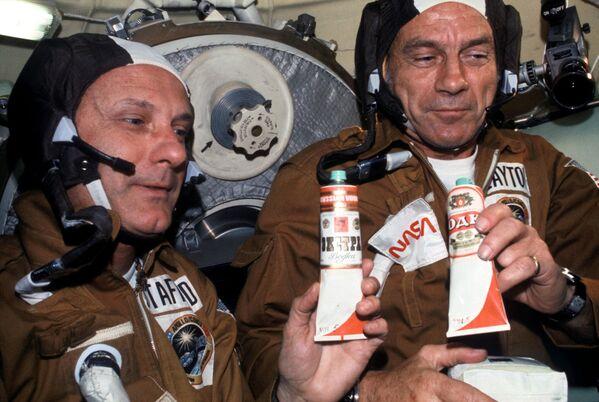 Astronauti Thomas Patten Stafford a Donald Kent Slayton s tubičkami boršče a vodky poté, co došlo ke spojení lodí Sojuz-Apollo ve vesmíru. - Sputnik Česká republika