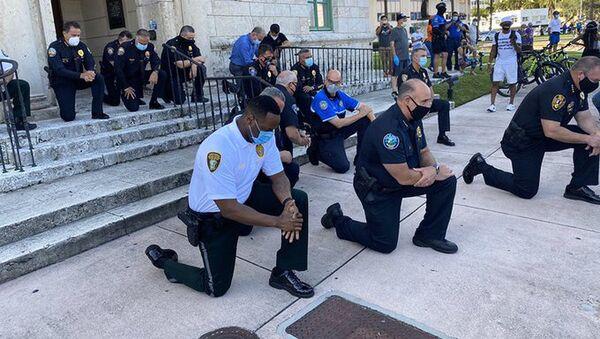 Američtí policisté v Miami klečí před demonstranty - Sputnik Česká republika