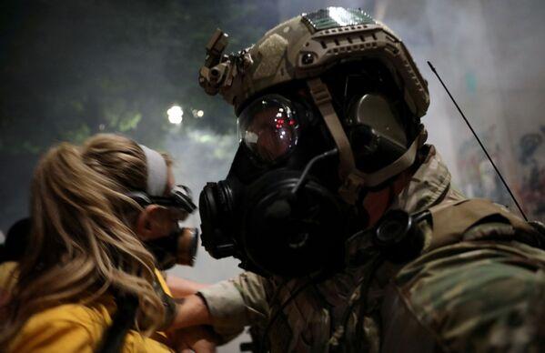 Policejní důstojník odstrkuje ženu během protestu v americkém Portlandu, stát Oregon.   - Sputnik Česká republika