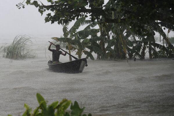 Muž v lodi během povodně v Doharu, Bangladéš.  - Sputnik Česká republika