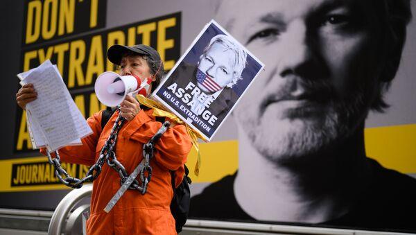 Žena protestuje za osvobození Juliana Assangeho v Londýně - Sputnik Česká republika