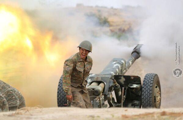 Arménský voják střílí z dělostřelecké zbraně při boji s ázerbájdžánskými jednotkami v Náhorním Karabachu - Sputnik Česká republika