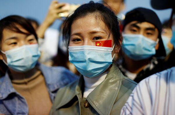 Lidé v maskách na slavnostním ceremoniálu vztyčení vlajky na náměstí Tchien-an-men na počest 71. výročí založení ČLR - Sputnik Česká republika