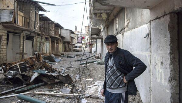 Мужчина на разрушенной улице города Степанакерт, который подвергся обстрелу - Sputnik Česká republika
