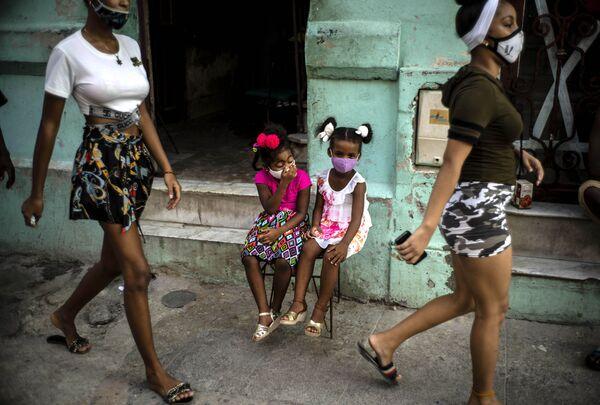 Dívky v rouškách čekají na své rodiče. Havana, Kuba - Sputnik Česká republika