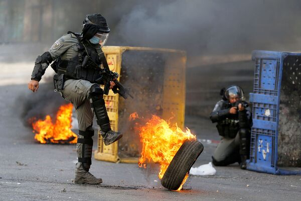 Důstojník izraelské policie kope do hořící pneumatiky během protiizraelské protestní akce v Hebronu na Západním břehu Jordánu - Sputnik Česká republika