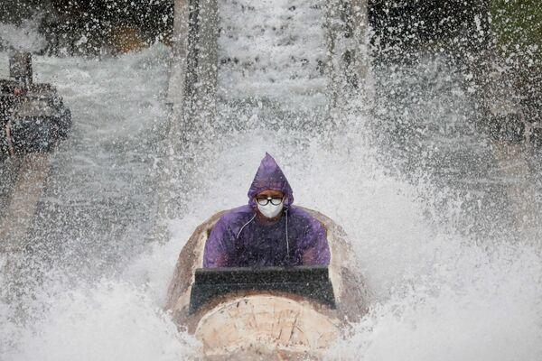 Muž v ochranné masce se baví v zábavním parku v Santa Rose, Filipíny - Sputnik Česká republika