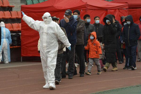 Pracovník v ochranném obleku vede lidi do dočasného testovacího centra ve městě Tchien-ťin. - Sputnik Česká republika