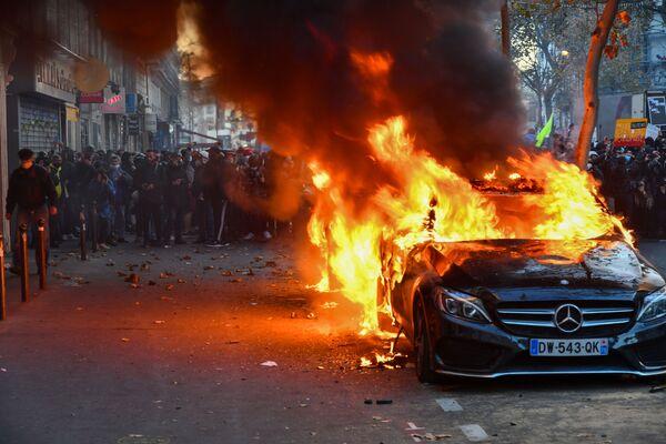 Hořící auto během protestní akce. - Sputnik Česká republika