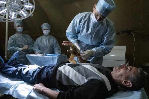 Lékař pomáhá pacientovi v polní nemocnici - Sputnik Česká republika