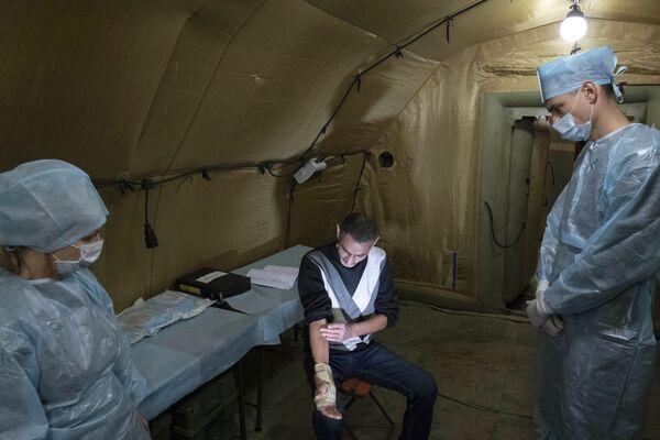 Lékaři poskytují pomoc pacientovi v polní nemocnici - Sputnik Česká republika