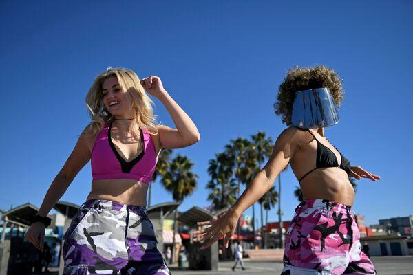Dívky na pláži v Los Angeles den před rozvolňováním protikoronavirových opatření. - Sputnik Česká republika