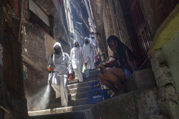 Dobrovolník provádí dezinfekci ve favelách, Rio de Janeiro. - Sputnik Česká republika