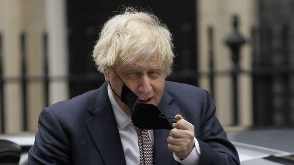 Премьер-министр Великобритании Борис Джонсон снимает маску - Sputnik Česká republika