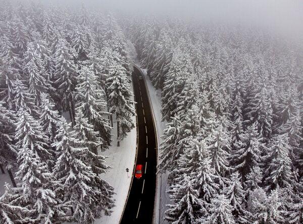 Auto na silnici vedoucí skrz zasněžený les nedaleko Frankfurtu, Německo - Sputnik Česká republika