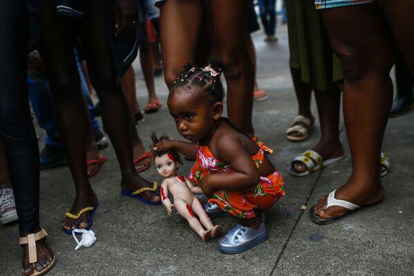 Holčička s panenkou v ruce během protestu proti zabití zbloudilými kulkami jejích sestřenic v Brazílii, když si hrály před svými domovy - Sputnik Česká republika