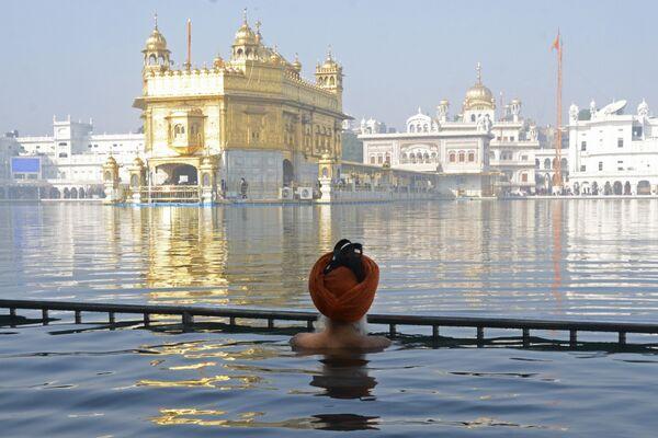 Sikh se koupou v posvátném sarovaru Zlatého chrámu - Sputnik Česká republika