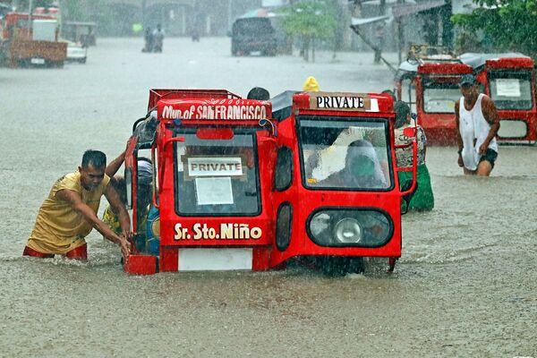 Lidé tlačí tříkolky přes zaplavené ulice, Filipíny - Sputnik Česká republika