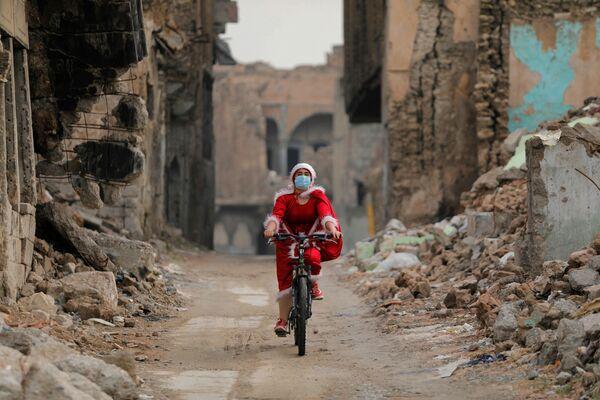 Dívka oblečená jako Santa Claus jezdí po ulici Mosulu, Irák - Sputnik Česká republika