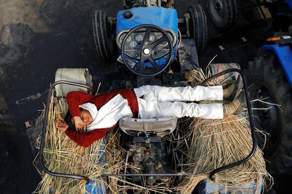 Syn farmáře spí v traktoru během protestu proti novým zemědělským zákonům na hranici Delhi-Uttar Pradesh, Indie - Sputnik Česká republika