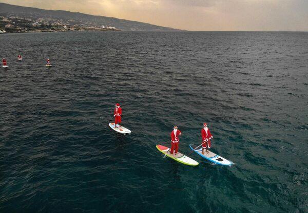 Lidé v kostýmech Santa Clause na dovolené v blízkosti Batrunu, Libanon - Sputnik Česká republika