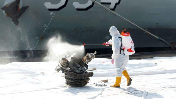 Zaměstnanec Červeného kříže nastříká dezinfekční prostředek na fragment turbíny letadla Sriwijaya Air, které se zřítilo v Jávském moři - Sputnik Česká republika