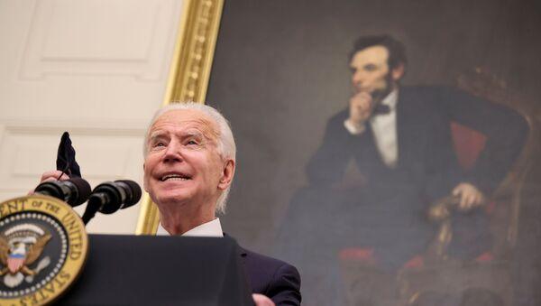 S portrétem bývalého prezidenta Abrahama Lincolna visícím v pozadí americký prezident Joe Biden hovoří o plánech své administrativy v boji proti pandemii koronaviru - Sputnik Česká republika