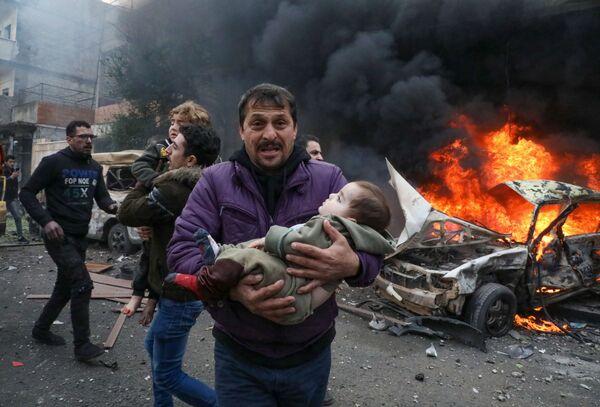 Muž nese dítě zraněné při výbuchu bomby v automobilu v syrském městě Azáz. - Sputnik Česká republika