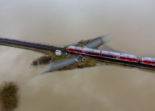 Vlak jede po železnici v zatopené krajině v Německu. - Sputnik Česká republika