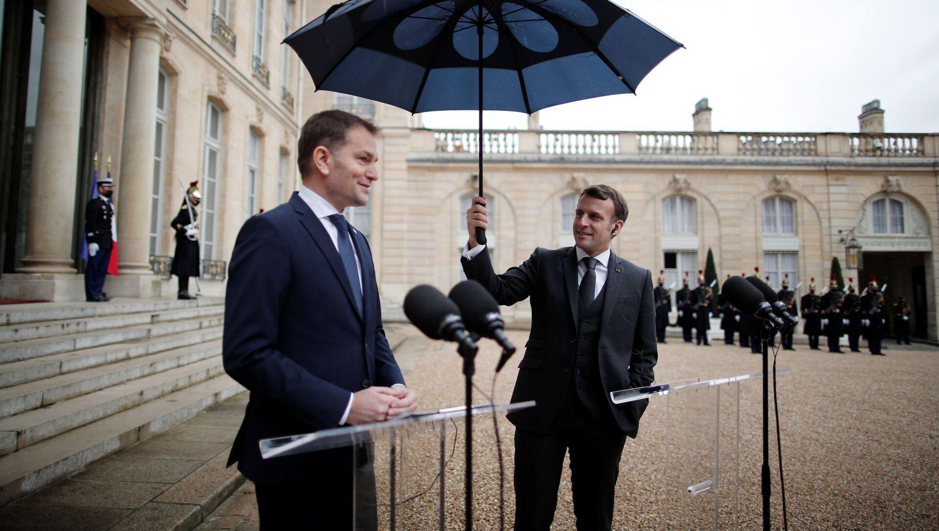 Francouzský prezident Emmanuel Macron drží deštník vedle slovenského premiéra Igora Matoviče během společného prohlášení v Elysejském paláci v Paříži - Sputnik Česká republika, 1920, 09.02.2021