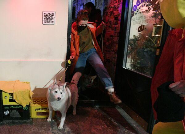 Návštěvník se svým mazlíčkem u vchodu do baru Underdog v Moskvě.  - Sputnik Česká republika