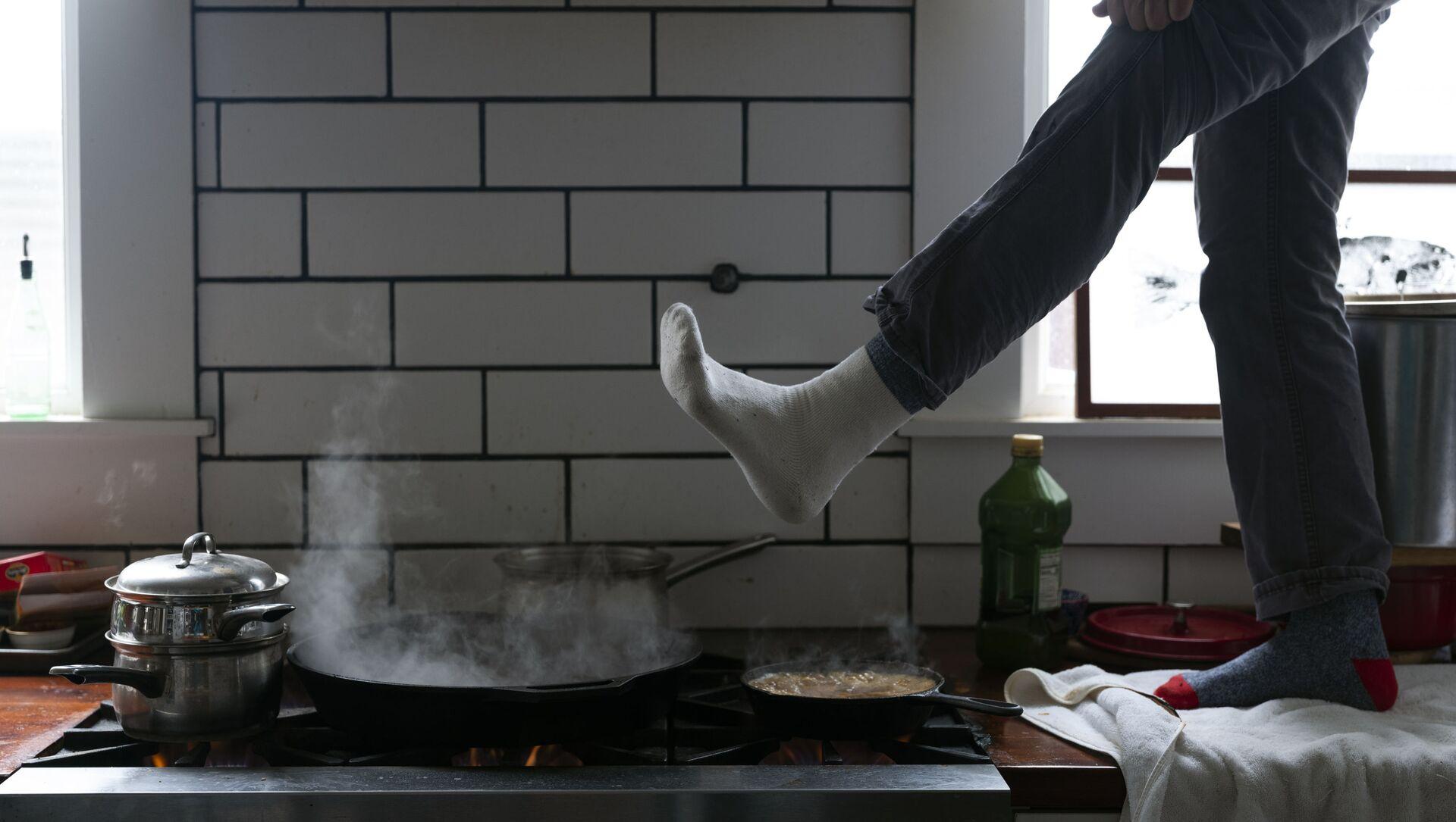Muž si ohřívá nohy nad plynovým sporákem v Austinu v Texasu v USA - Sputnik Česká republika, 1920, 17.02.2021