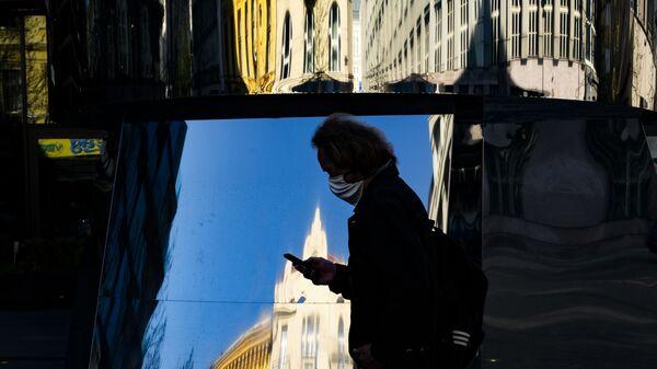 Прохожий в медицинской маске и с мобильным телефоном в Праге - Sputnik Česká republika