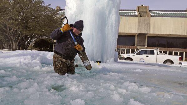 Pracovník láme led ve zmrzlé fontáně v Richardsonu v Texasu v USA - Sputnik Česká republika