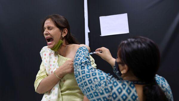 Zaměstnanec indického institutu Serum Institute of India během očkování proti covidu-19 indickou vakcínou CoviShield od společnosti AstraZeneca - Sputnik Česká republika