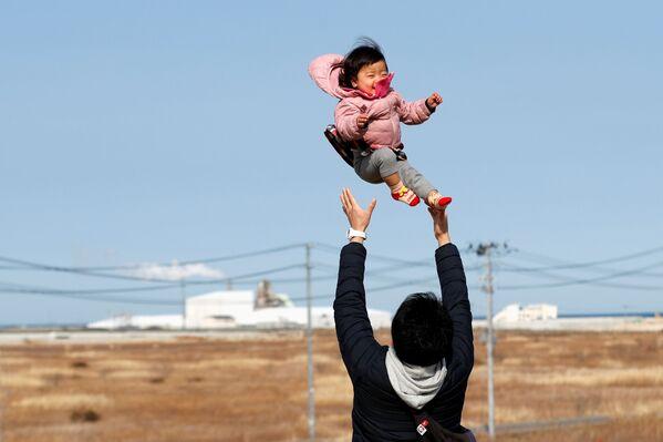 Muž, který přišel o své příbuzné během zemětřesení v roce 2011, se svým synem v prefektuře Fukušima. - Sputnik Česká republika