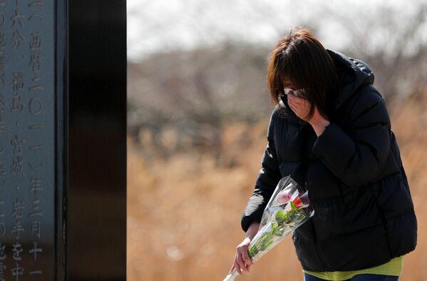 Žena klade květiny k památníku obětí zemětřesení r. 2011. - Sputnik Česká republika