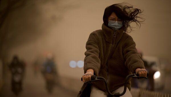Dívka během písečné bouře v Pekingu - Sputnik Česká republika