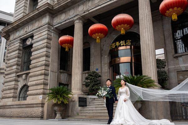 Novomanželé na ulici ve Wu-chanu v Číně. - Sputnik Česká republika
