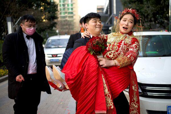 Ženich nese nevěstu do hotelu po svatbě ve Wu-chanu v Číně. - Sputnik Česká republika