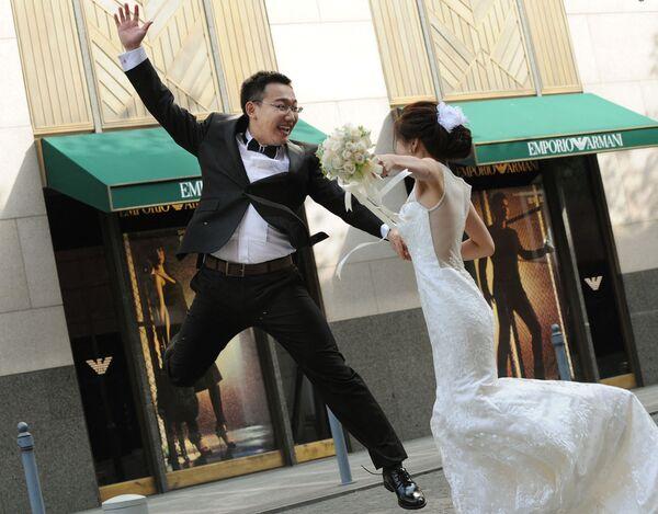 Ženich skáče vedle nevěsty během svatebního focení v Šanghaji.   - Sputnik Česká republika