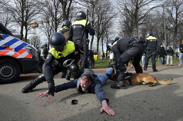 Policisté při zadržení účastníka protivládní demonstrace v nizozemském Haagu. - Sputnik Česká republika