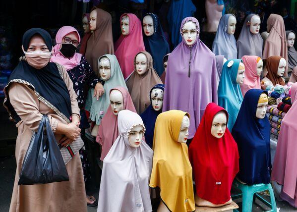 Ženy v  rouškách stojí vedle hidžábů na prodej na textilním trhu Tanah Abang v indonéské Jakartě. - Sputnik Česká republika
