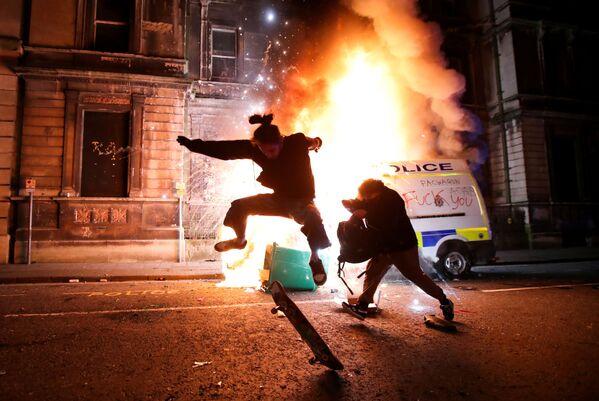Demonstrant ujíždí na skateboardu před hořícím policejním autem při protestu v Bristolu, Velká Británie. - Sputnik Česká republika