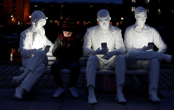 """Chlapec pózuje se sochou """"pohlceni světlem"""" vytvořenou umělcem Gali May Lucasem v Liverpoolu, Velká Británie. - Sputnik Česká republika"""