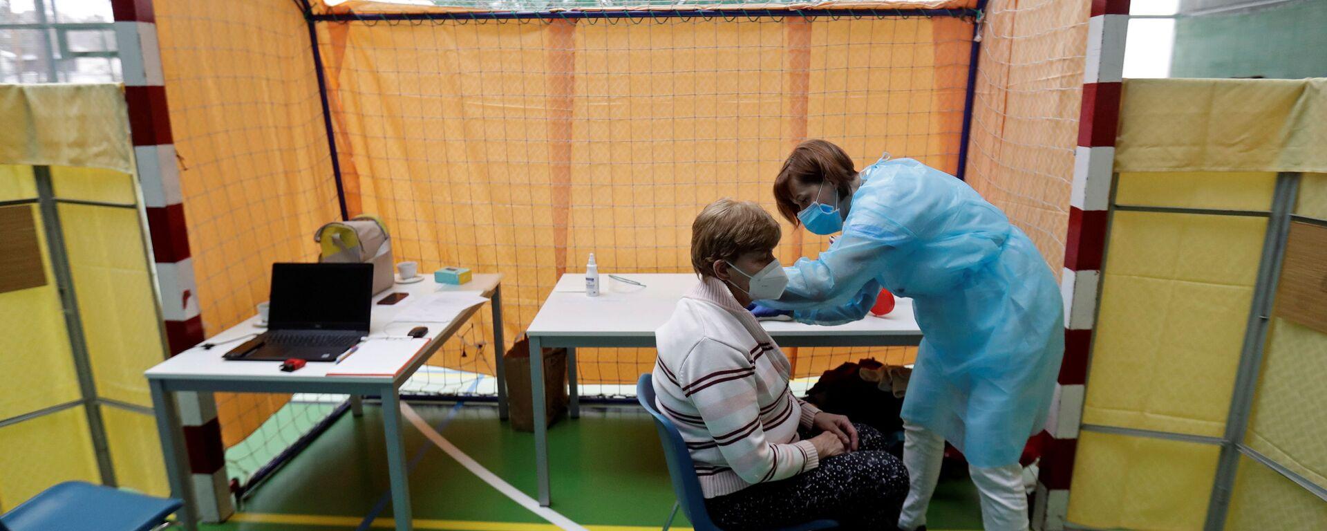 Zdravotník očkuje ženu proti koronaviru v centru hromadné vakcinace v tělocvičně v Praze - Sputnik Česká republika, 1920, 12.07.2021