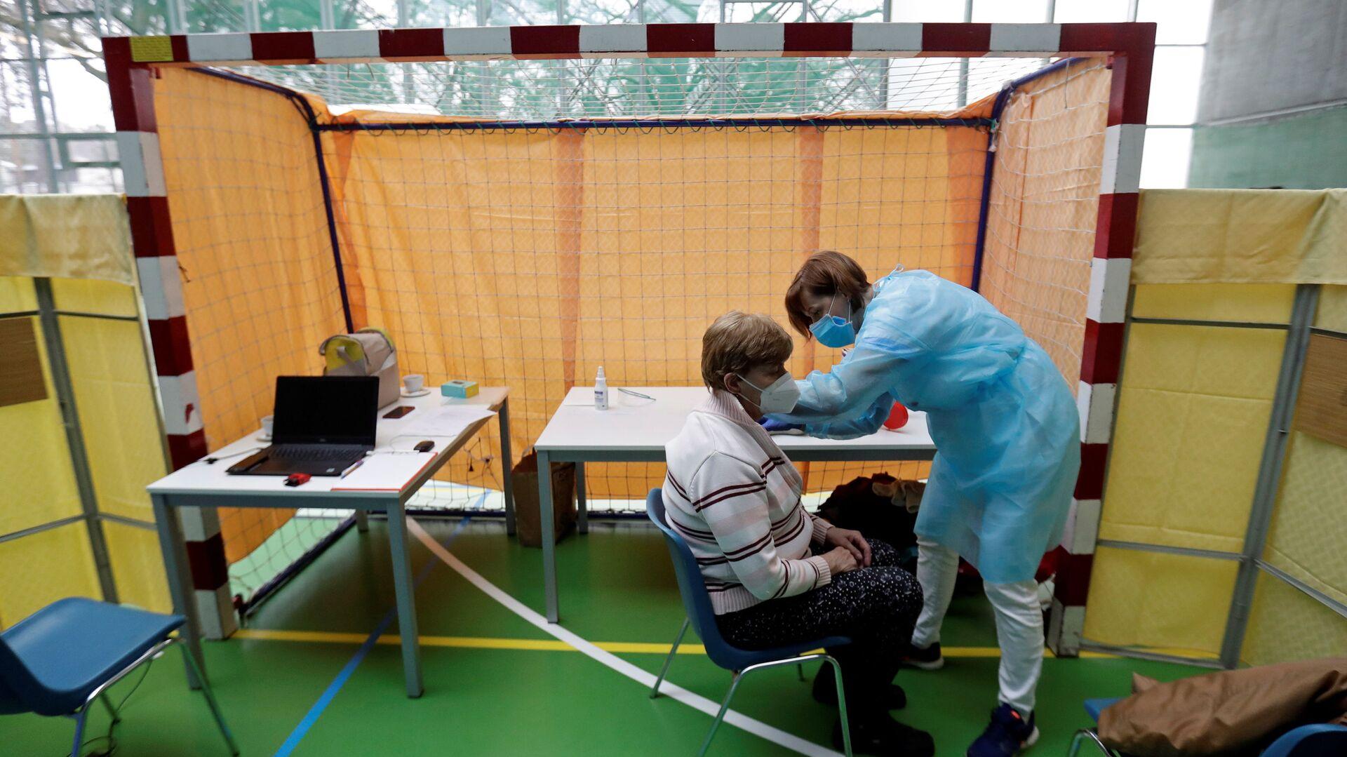 Zdravotník očkuje ženu proti koronaviru v centru hromadné vakcinace v tělocvičně v Praze - Sputnik Česká republika, 1920, 02.08.2021