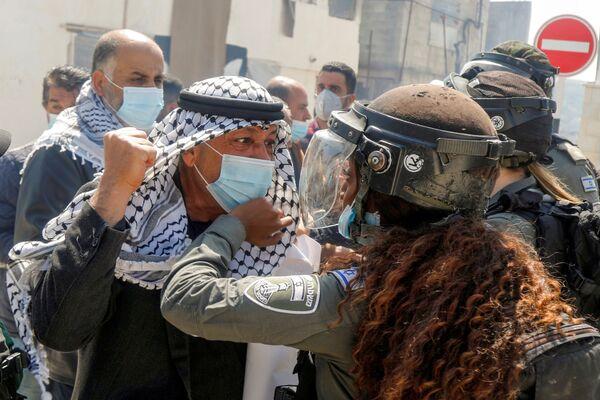 Palestinský demonstrant se pere se ženou z pohraniční stráže během protestní akce. - Sputnik Česká republika
